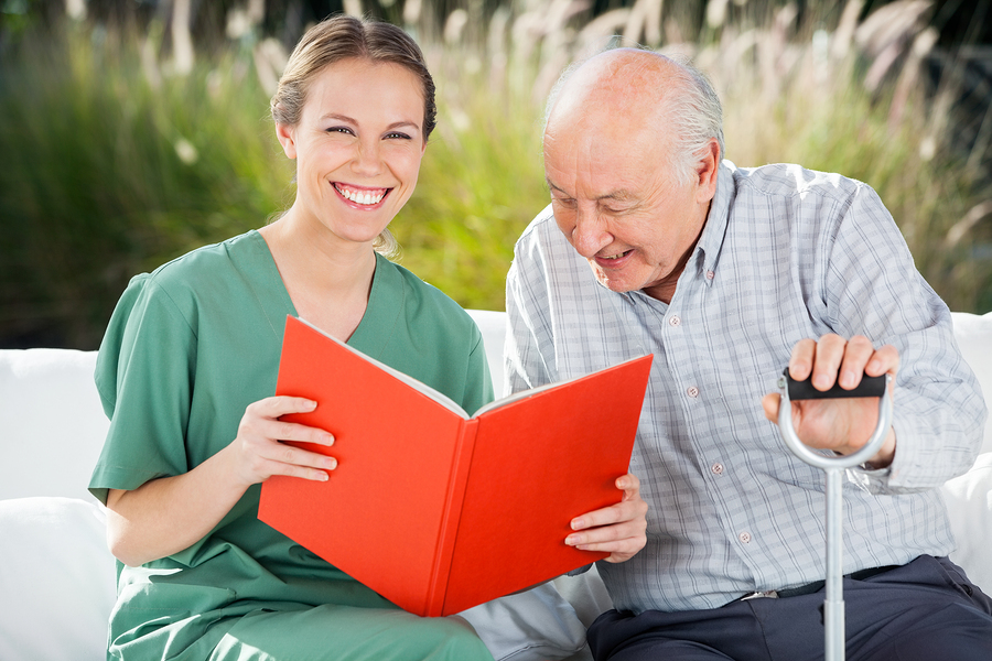 Portrait of happy female nurse reading book for senior man at nu